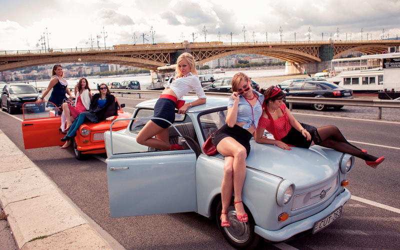 A group of women climbing across Trabant vehicles