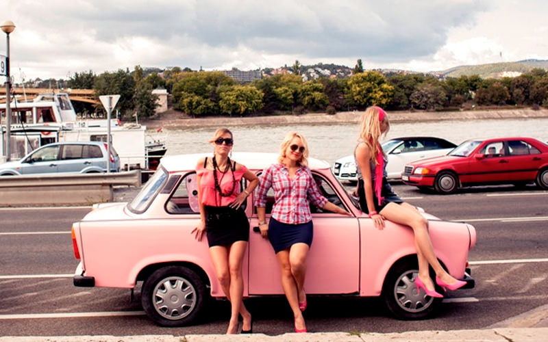 A group of women sitting on Trabant vehicles