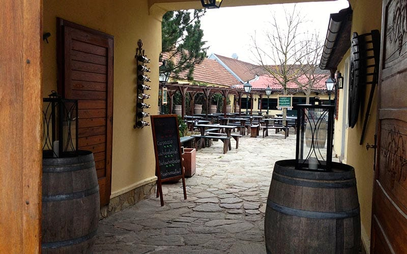 A courtyard with seats and wooden barrels as tables