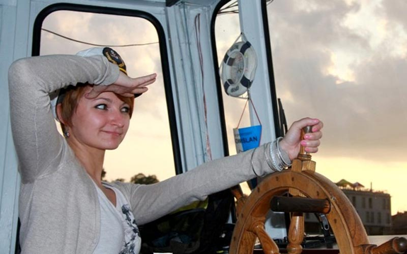 A woman at the steering wheel of a boat