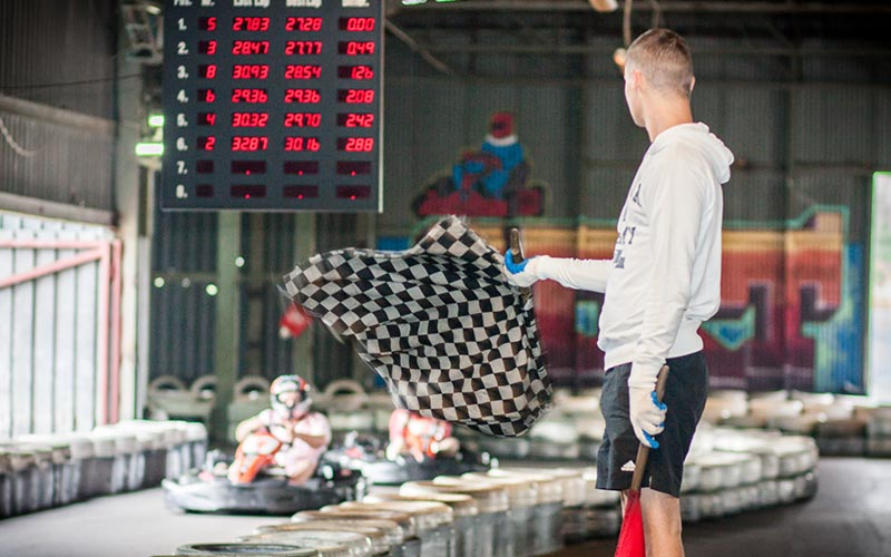 A man waving a checkered flag at people in go karts