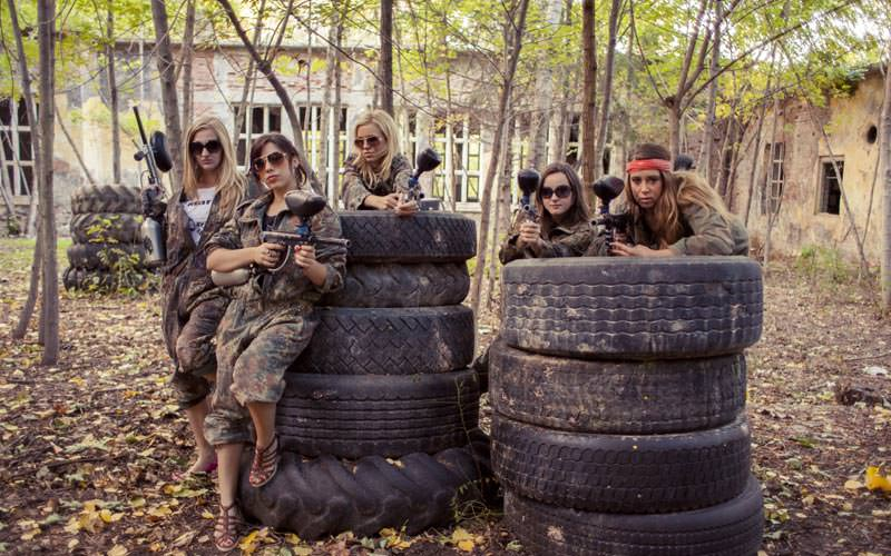 Image of a group of women dressed in camoflauge clothing and holding paintball guns standing against and behind a pile of tyres wearing sunglasses