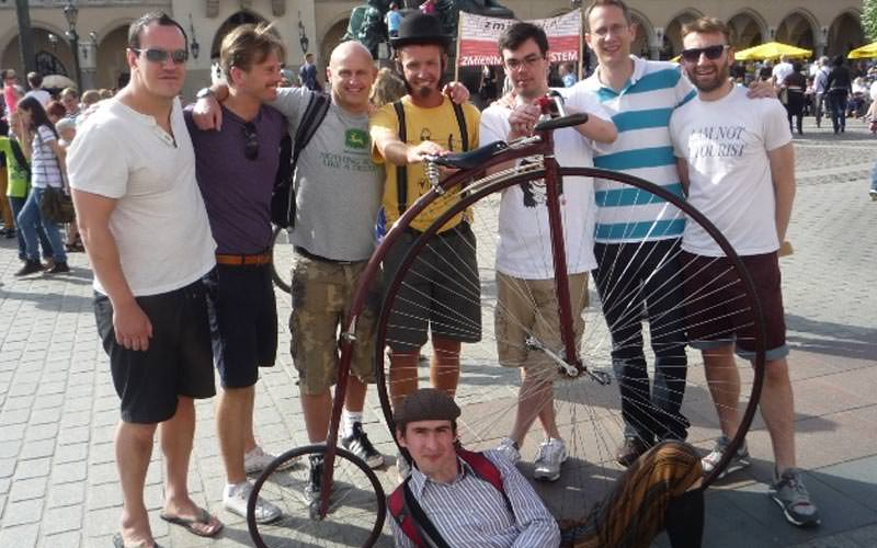 Imsge of a group of guys standing around a penny farthing with a guy lying on the floor wearing a grandad cap with a striped shirt and braces