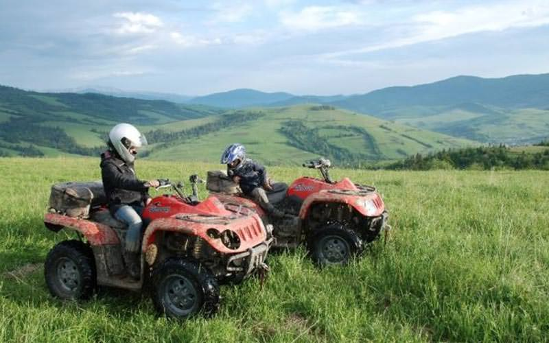 Image of two people on red quad bikes in a field surrounded by hills wearing helmets