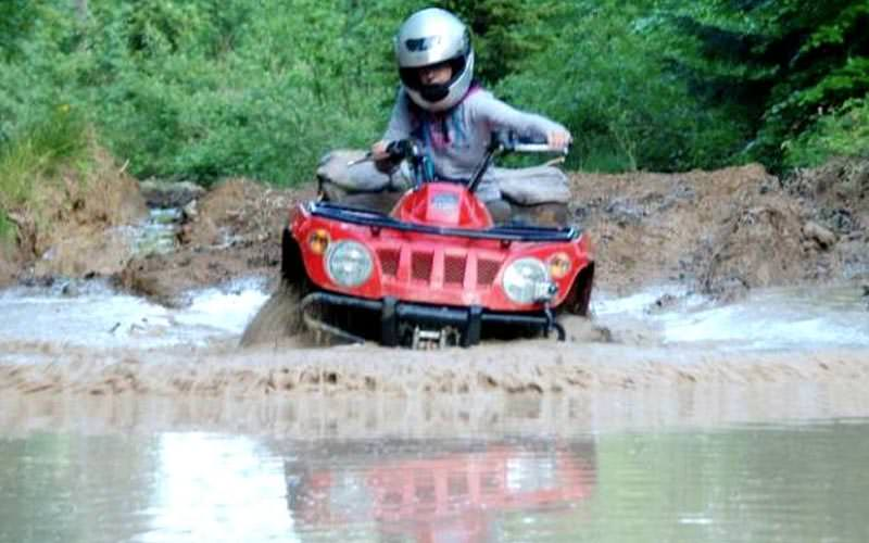 Image of someone driving a red quad bike through a big puddle of water wearing a helmet