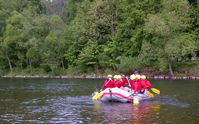 Image of a group of people in a raft with yellow owes and red life jackets and yellow helmets in the water
