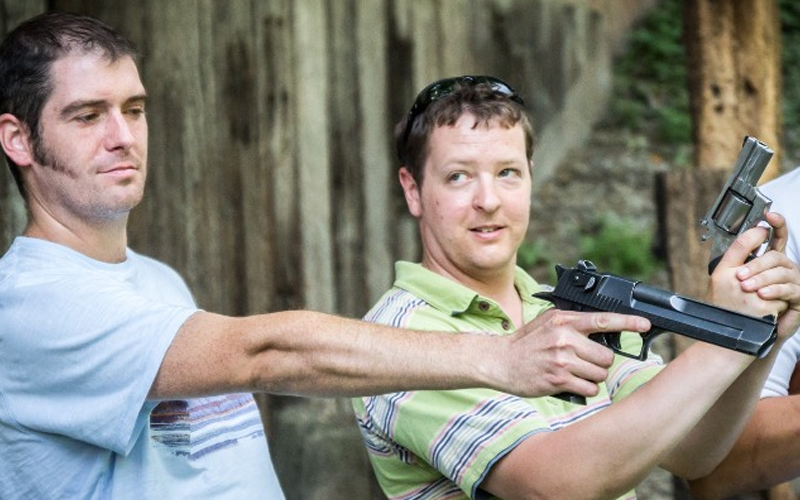 Two men holding handguns at a shooting range