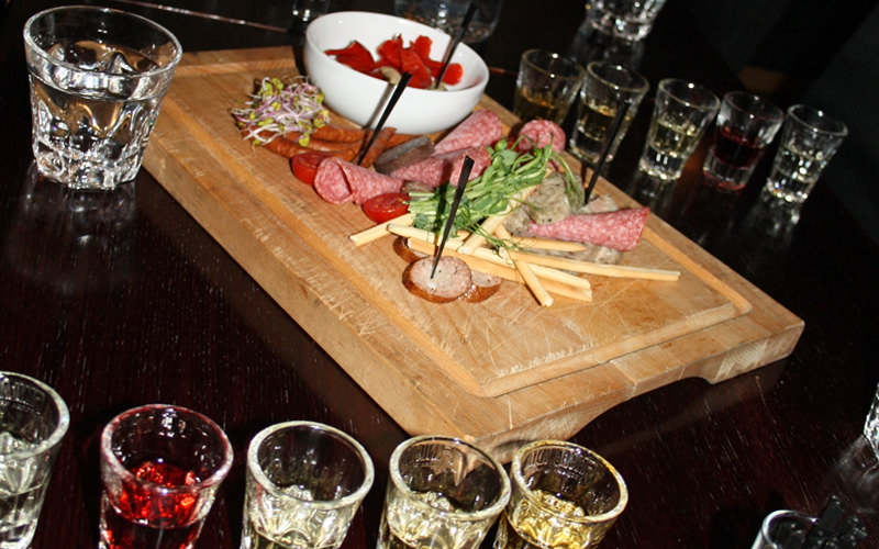 A selection of vodka complimented with a plate of various meats