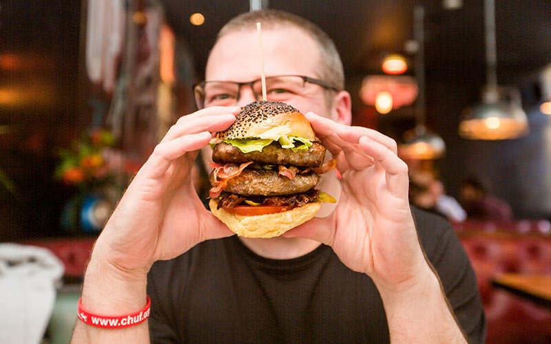 man eating a massive double burger, wearing a chuf charity wrist band