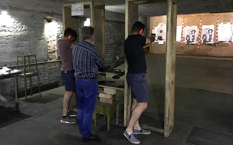 Image of two guys standing in between a wooden frame aiming guns at targets on a wall wearing ear muffs