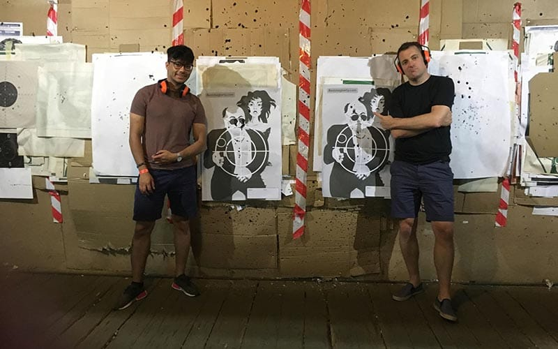Image of two men standing beside targets