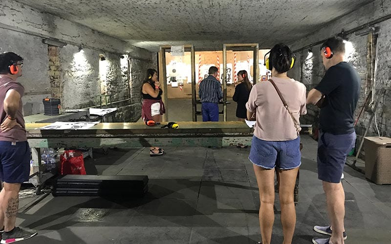 Image of a group of people at a indoor shooting range wearing ear muffs