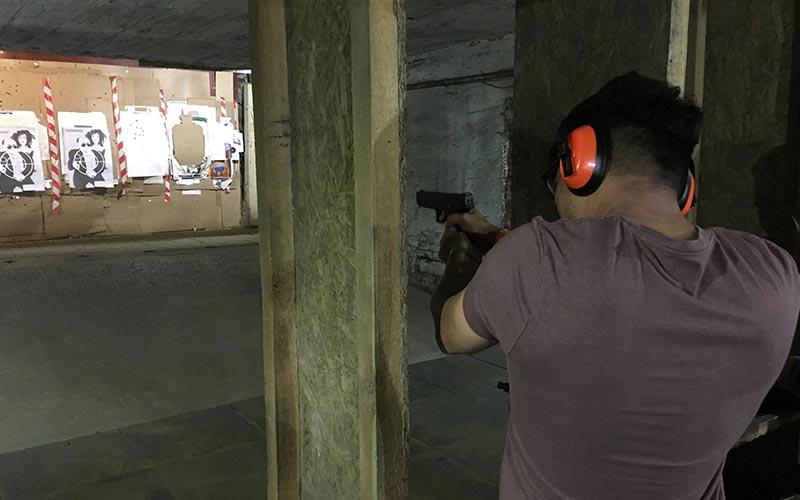 A man aiming a gun at a target