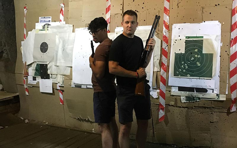 Two men holding guns in front of a target