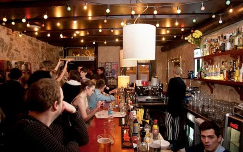 Image of a group of people inside a pub standing at the bar
