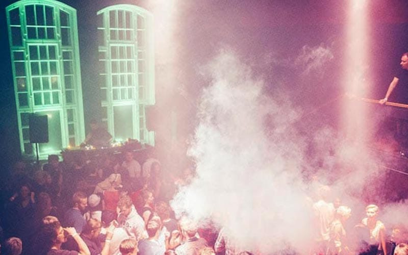 Image of a club with people on the dancefloor with smoke being blown and neon lighting