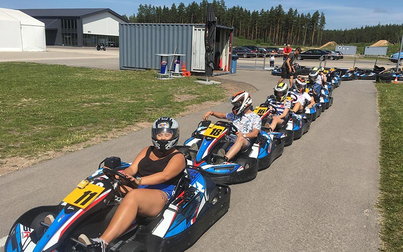 A group of people sitting in go karts on an outside track