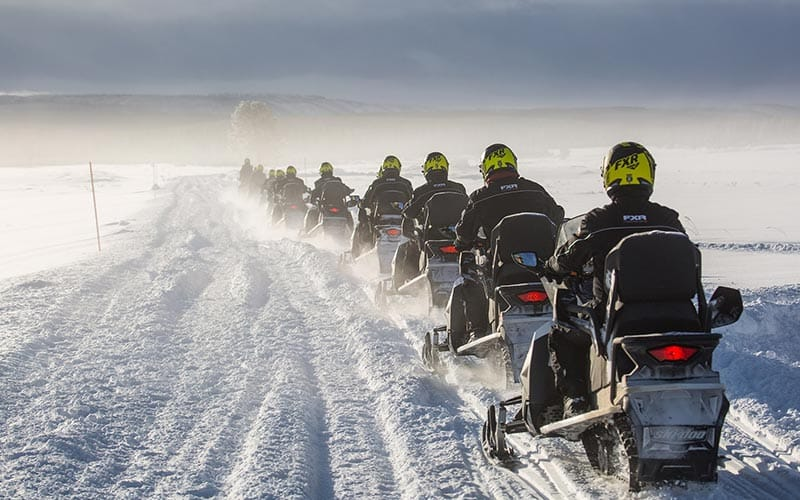 Image of a group on snowmobiles a snowed track in a line