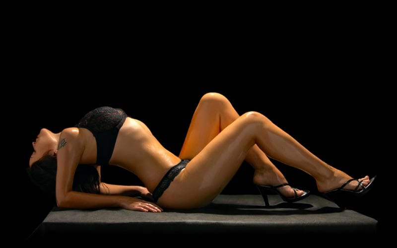 Image of a woman lying back on a table in black underwear and black heeled shoes