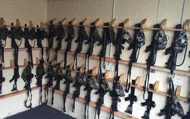 Room with two rails of paintball guns lined up on the walls.
