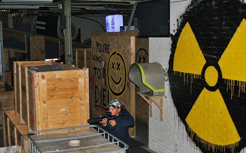 Large nuclear logo painted on near wall, with man shooting paintballs behind a wooden box in the middle of the picture.