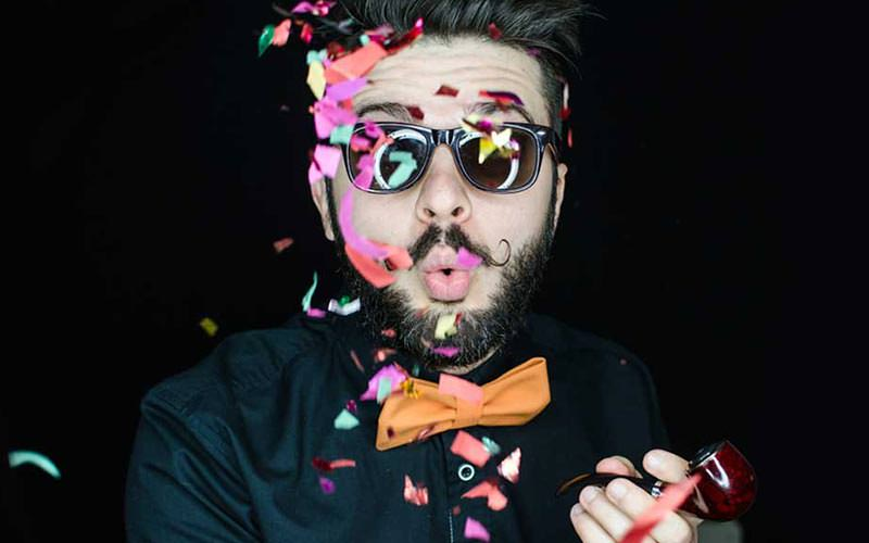 A man posing while confetti falls in front of him