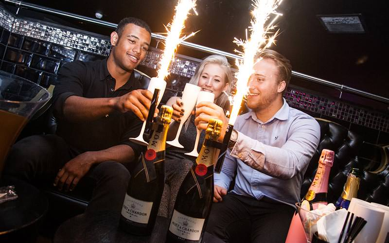 Two men and one woman holding champagne glasses while sparklers are lit around them
