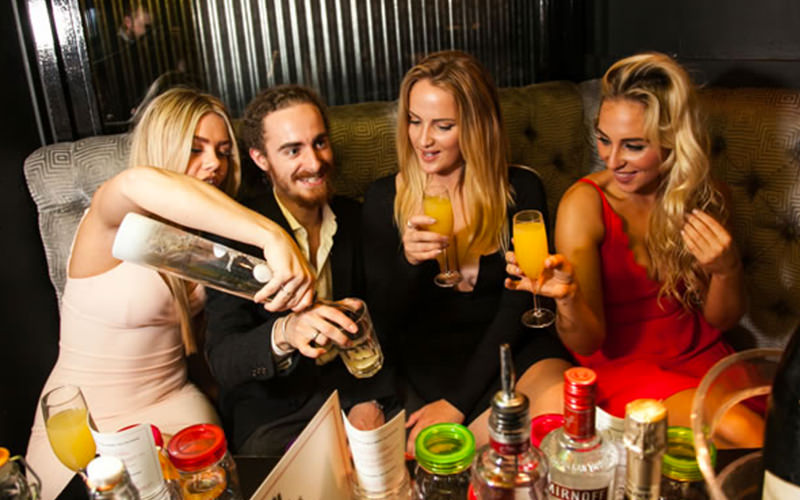 A group of three women and a man enjoying drinks at a nightclub table