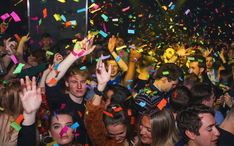 A crowd dancing in a nightclub while confetti falls from the ceiling