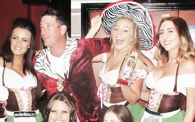 Woman wearing a zebera print cowboy hat with friends in the pub