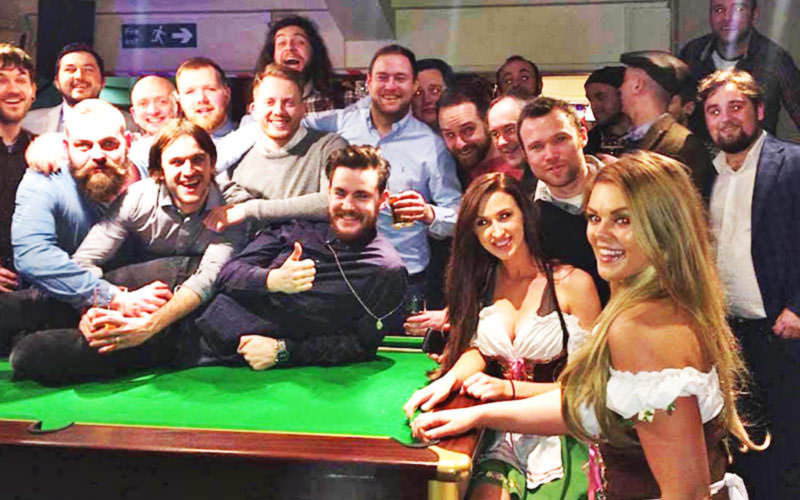 Men stood around a pool table with women dressed as Bavarian beer maids