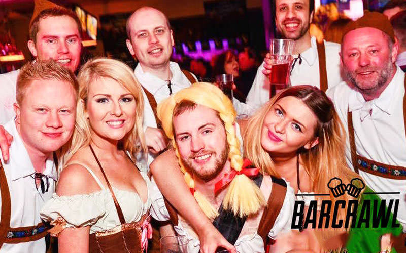 Man wearing a yellow pigtails wig and bavarian costume surrounded by friends and sexy women in a pub