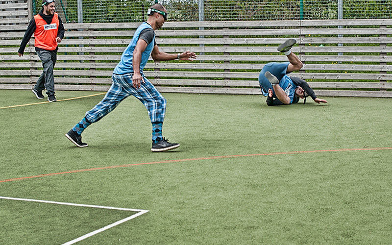 Image of three men, wearing googles on astroturf pitch with one of the players falling over.
