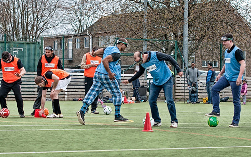 Two groups in blue and orange bibs, all wearing googles, trying to dribble footballs around the red cones.