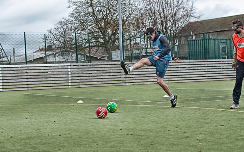 Man in blue bib attempting to kick a red or green football on an astroturf pitch.