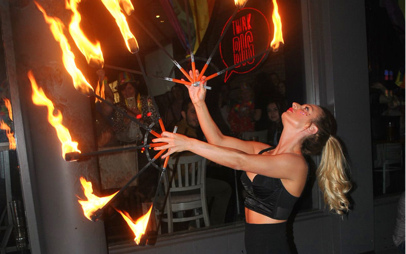 A woman juggling with fire outside a nightclub