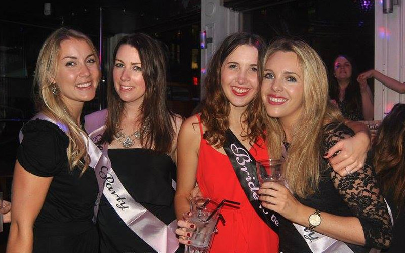 A group of women wearing hen party sashes