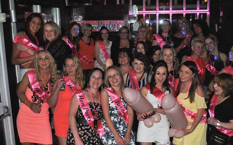 A group of women wearing hen party sashes and posing with novelty inflatables