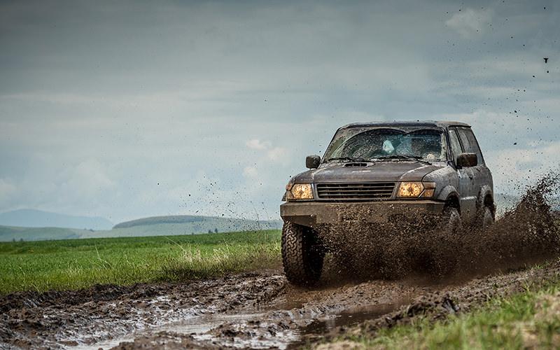 A 4x4 driving through mud as it sprays through the air