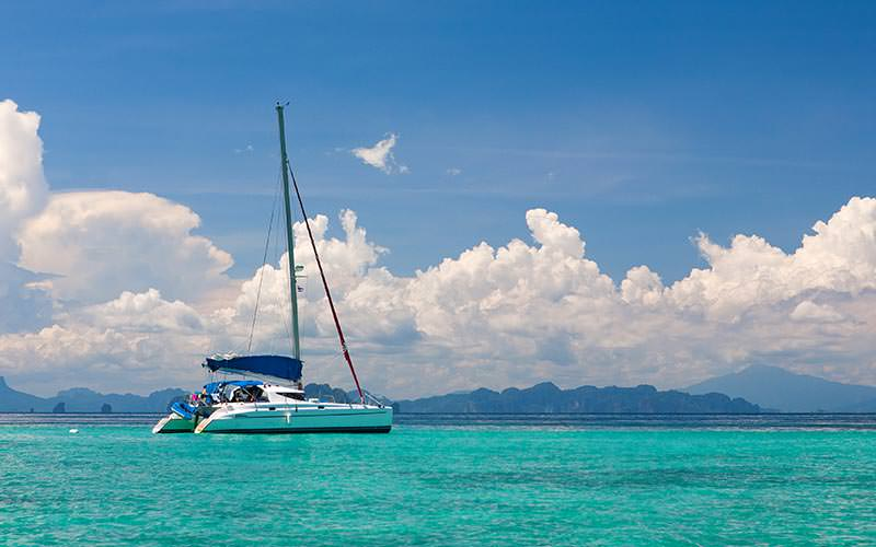 A catamaran out on the ocean with mountains in the background