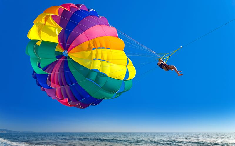 A woman parasailing above the sea with a colourful parachute