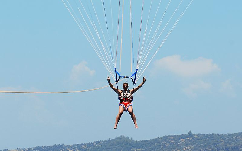 A man holding his arms in the air whilst attached to a paraglide