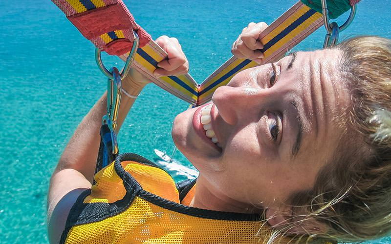 Close up of a woman's face turning around whilst paragliding to a backdrop of the sea