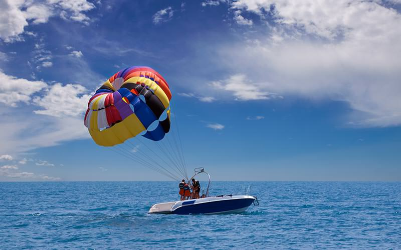 People on a boat attached to a colourful parachute