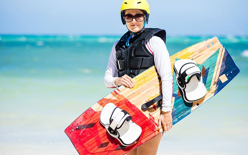 A woman in a life jacket and helmet, holding a colourful wakeboard, to a backdrop of the sea