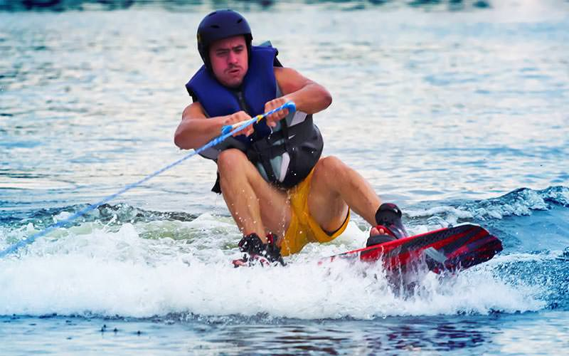 A man riding a wakeboard whilst holding onto a cable track