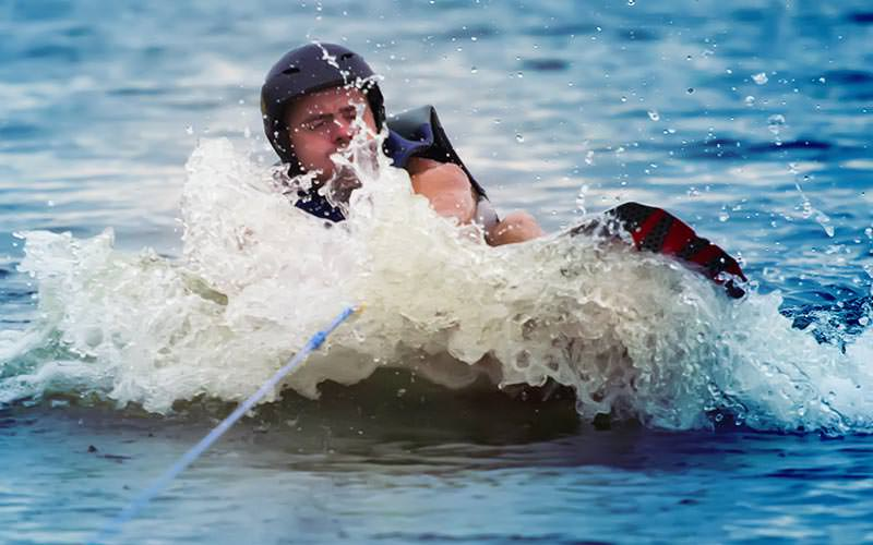 A man falling in the sea wakeboarding, whilst holding a cable track