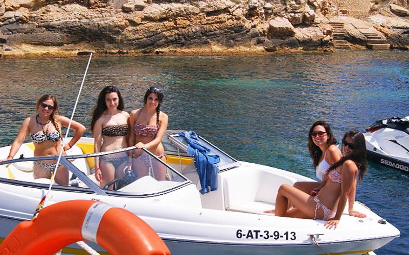 Five women on a white speedboat with rocks in the background