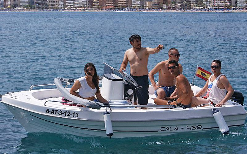 Four men and a woman sat on a white speedboat