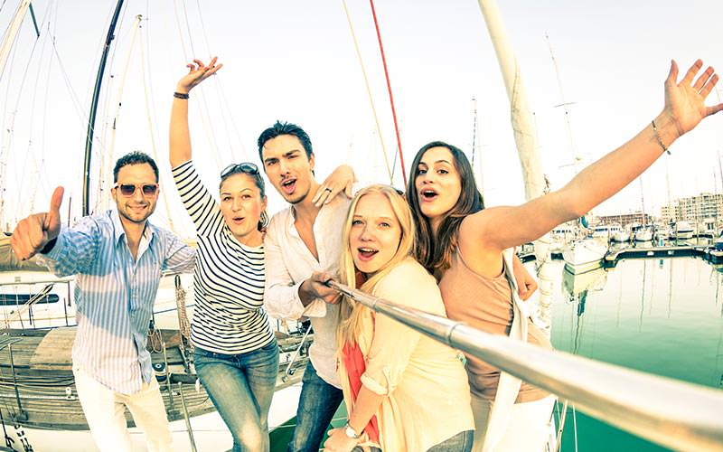 Men and women posing for a photo on a selfie stick with a marina in the background